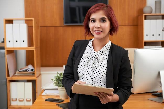 Portrait of smiling pretty female entrepreneur filling document on clipboard