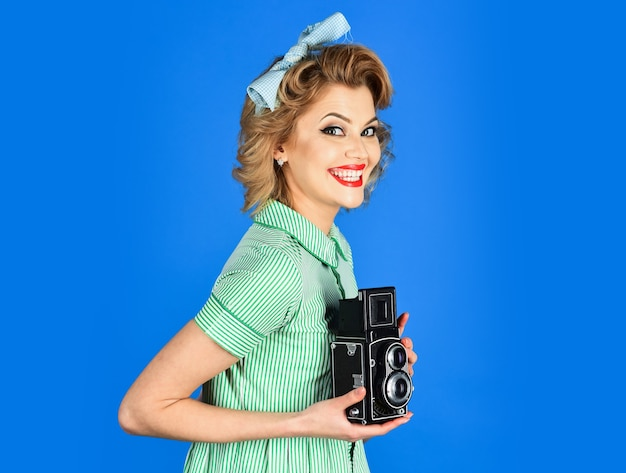 Portrait of a smiling pretty girl taking photo on a retro camera isolated over blue  journalism