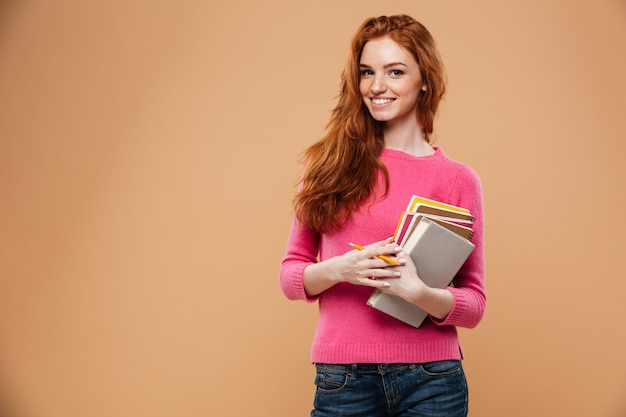 Portrait of a smiling pretty redhead girl holding books