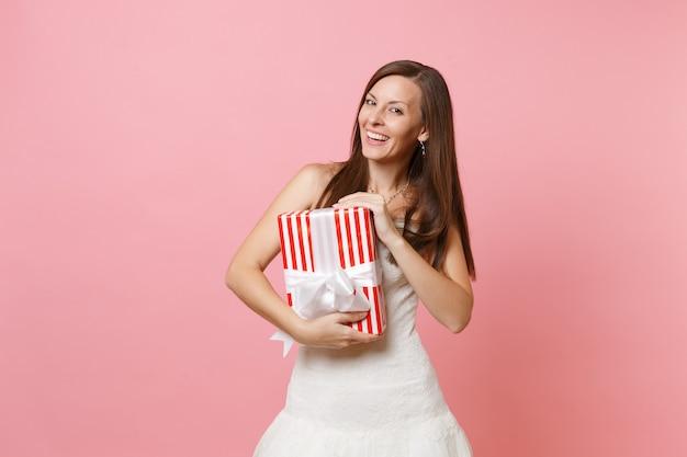 Ritratto di una bella donna sorridente in un bellissimo abito bianco che tiene in mano una scatola rossa con un regalo in regalo