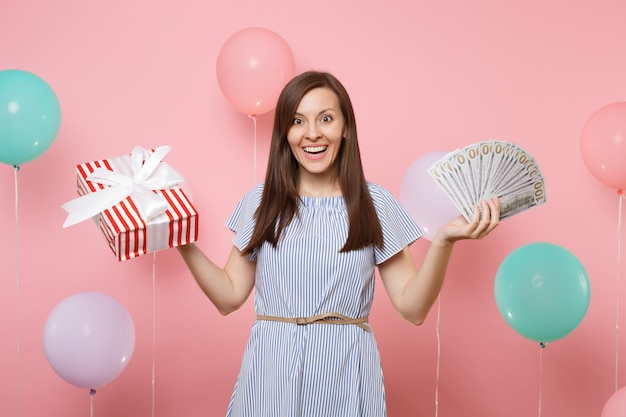 Portrait of smiling pretty woman in blue dress holding bundle lots of dollars cash money and red box with gift present on pink background with colorful air balloons. birthday holiday party concept.