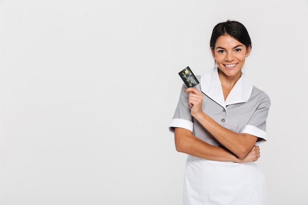 Portrait of smiling pretty woman in uniform holding credit card