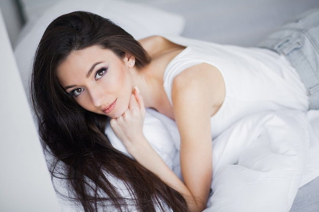 Portrait of a smiling pretty young brunette woman relaxing in white bed