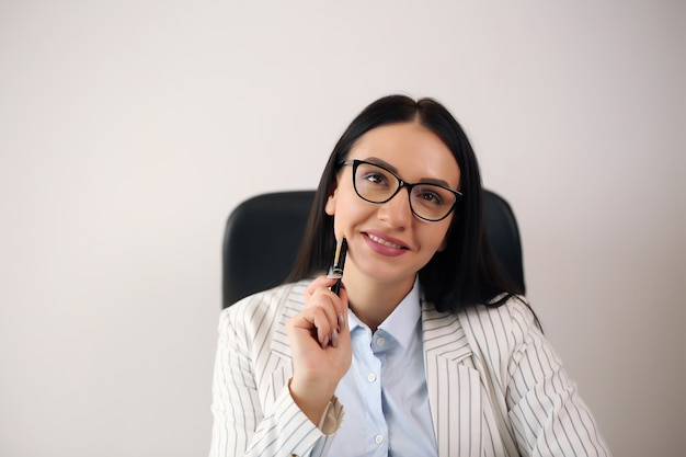 Portrait of smiling pretty young business woman in glasses sitting on workplace.