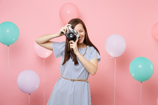 Portrait of smiling pretty young woman in blue dress take pictures on retro vintage photo camera on pink background with colorful air balloons. birthday holiday party people sincere emotions concept.
