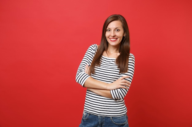 Portrait of smiling pretty young woman in casual striped clothes standing, holding hands folded