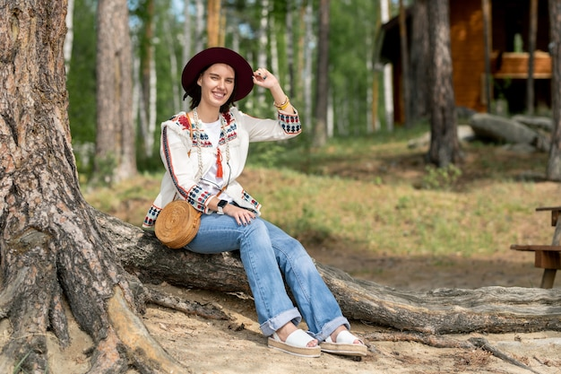 Portrait of smiling pretty young woman in jeans and hat sitting on root of tree while resting in recreation center