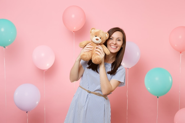 Portrait of smiling pretty young woman wearing blue dress holding teddy bear plush toy on pastel pink background with colorful air balloons. birthday holiday party, people sincere emotions concept.