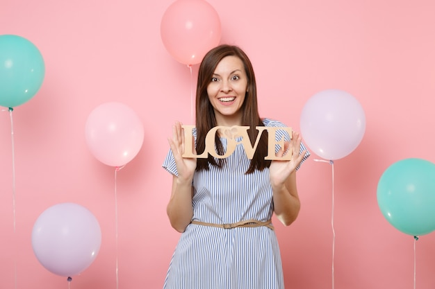 Portrait of smiling pretty young woman wearing blue dress holding wooden word letters love on pastel pink background with colorful air balloons. birthday holiday party people sincere emotions concept.