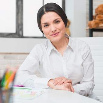 Portrait of smiling professional female psychologist sitting in her office