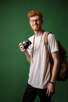 Portrait of smiling readhead bearded hipster with retro camera and backpack