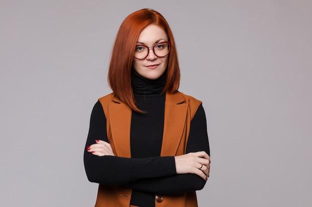 Ritratto di donna d'affari dai capelli rossi sorridente con gli occhiali in posa guardando la fotocamera a colpo medio. capo femminile europeo di bellezza che sta con la mano attraversata isolata al fondo bianco dello studio