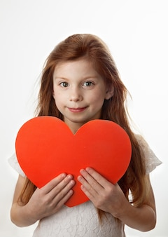 Portrait of smiling red-haired little girl holding big red heart in her hands on white background. love, valentines day, mothers day or fathers day concept.