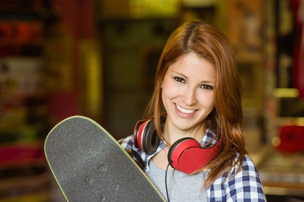 Portrait of a smiling redhead holding her skateboard