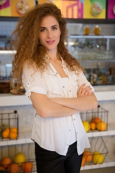 Portrait of smiling redhead waitress standing with arms crossed