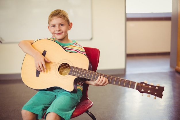 Portrait of smiling schoolboy playing guitar in classroom