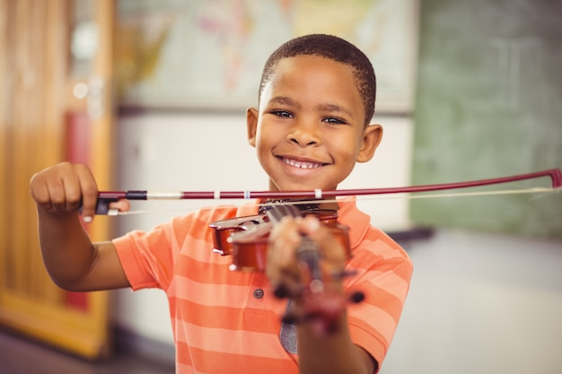 Portrait of smiling schoolboy playing violin in classroom