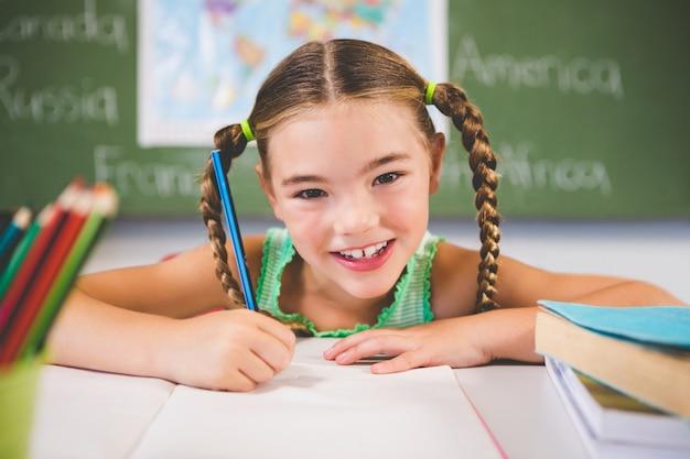 Portrait of smiling schoolgirl doing homework in classroom