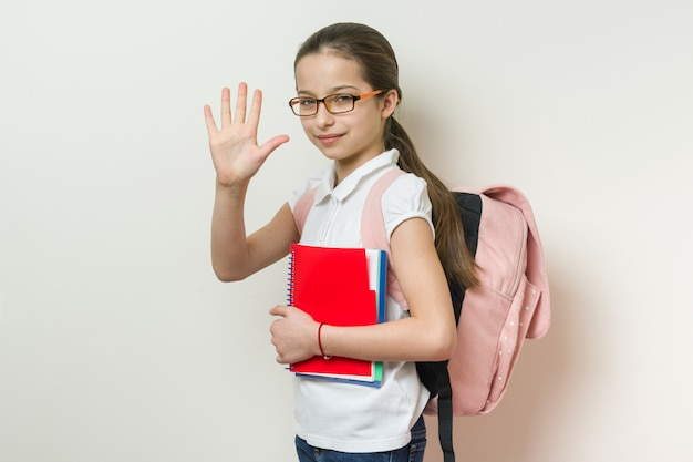 Portrait of a smiling schoolgirl giving high five to camera