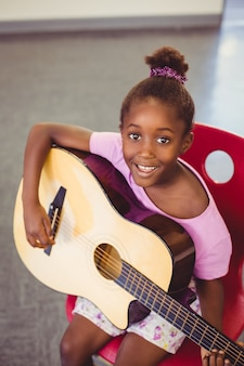 Portrait of smiling schoolgirl playing guitar in classroom