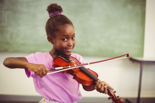 Portrait of smiling schoolgirl playing violin in classroom