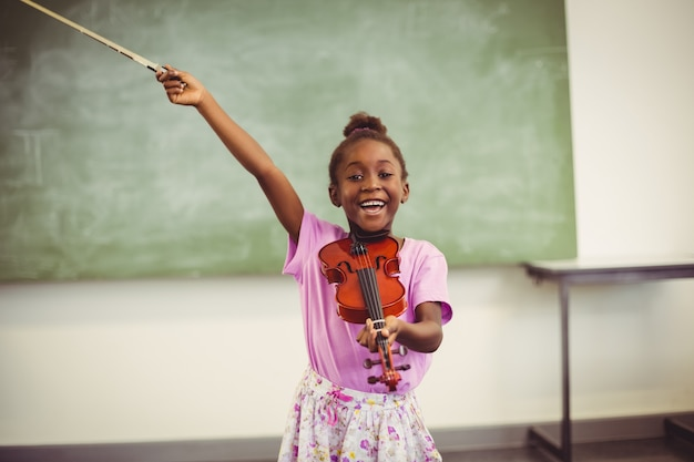Portrait of smiling schoolgirl playing violin in classroom
