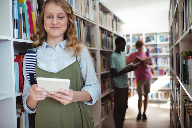 Portrait of smiling schoolgirl standing with digital tablet in library