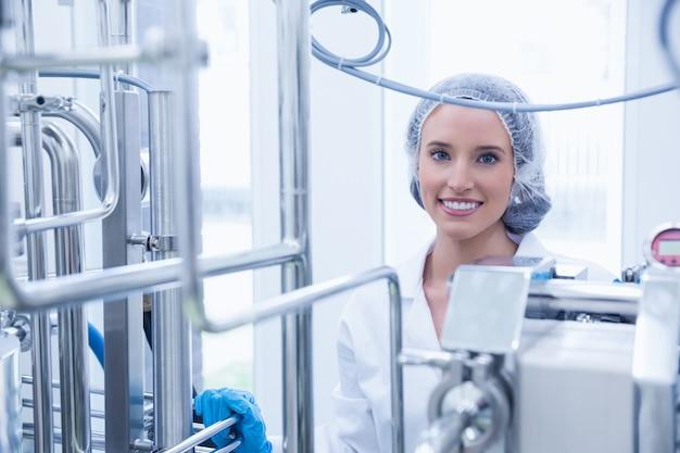 Portrait of a smiling scientist behind metal pipe