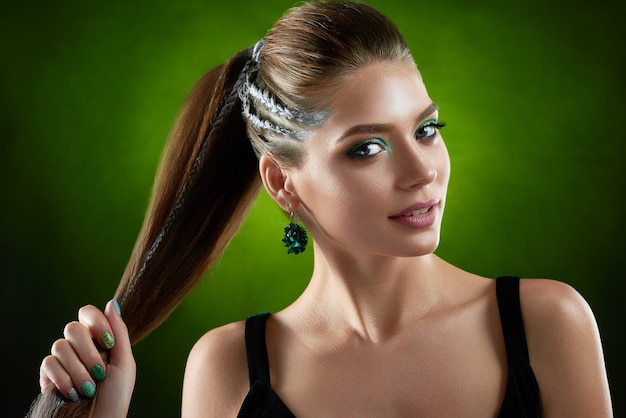 Portrait of smiling seductive woman with stylish hairstyle and makeup in green colors. beautiful brunette with big earring, holding hair at hand.