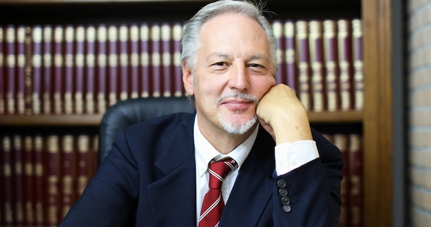 Portrait of smiling senior businessman in his library