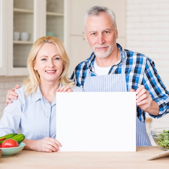 Portrait of a smiling senior couple showing white blank placard on wooden table