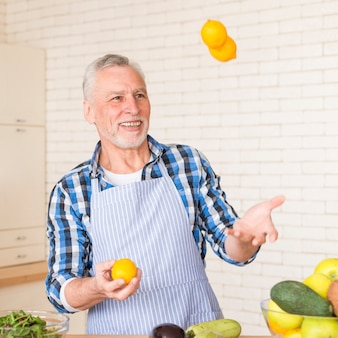 Portrait of a smiling senior man juggling whole lemons while preparing the kitchen