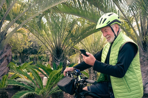 Portrait of a smiling senior man using smart phone while bike ride in outdoor tropical place. white-haired retiree enjoying his free time