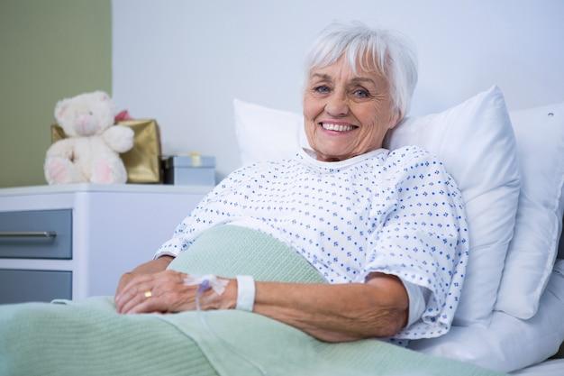 Portrait of smiling senior patient on bed