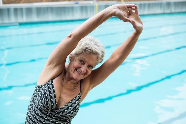 Portrait of smiling senior woman exercising at poolside
