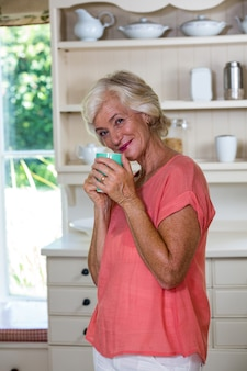 Portrait of smiling senior woman having coffee in kitchen