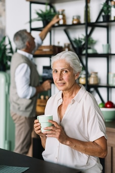 Portrait of smiling senior woman holding coffee cup