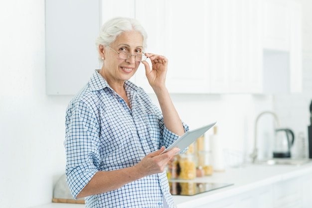 Portrait of smiling senior woman holding digital tablet standing in kitchen
