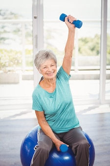 Portrait of smiling senior woman holding dumbbell