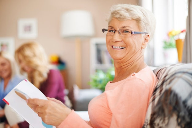 Portrait of smiling senior woman reading newspaper