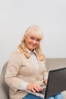 Portrait of smiling senior woman sitting on sofa using laptop