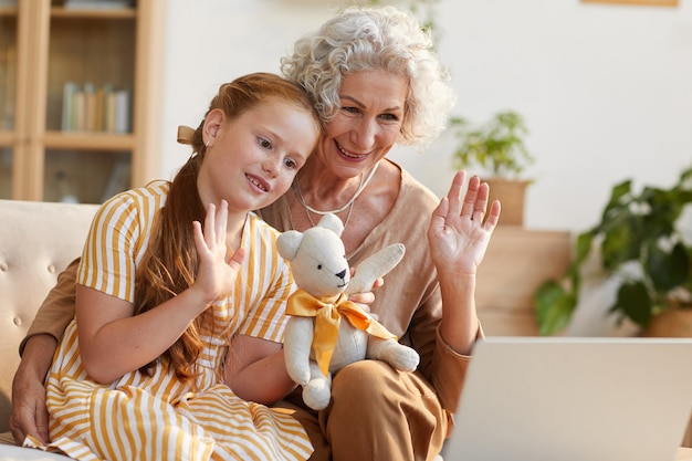Portrait of smiling senior woman waving at laptop camera during video call with cute granddaughter in cozy home interior