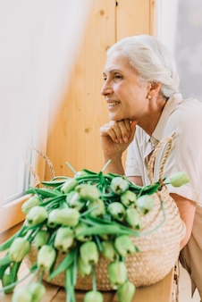 Portrait of smiling senior woman with basket of tulips