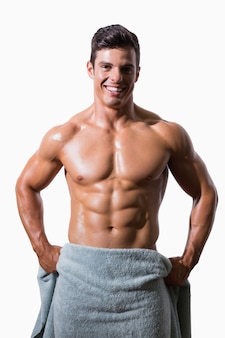 Portrait of a smiling shirtless muscular man wrapped in towel