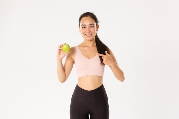 Portrait of smiling slim and fit asian fitness girl, workout coach advice eating vitamins and healthy food, pointing at green apple, white background.