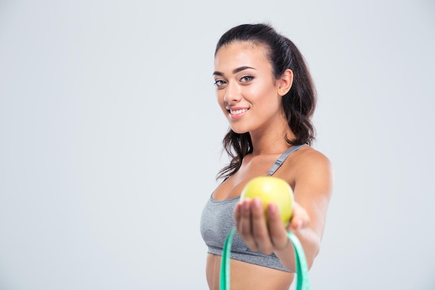 Portrait of a smiling sports woman holding apple and measuring type isolated on a white wall