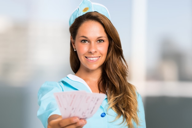 Portrait of a smiling stewardess holding tickets
