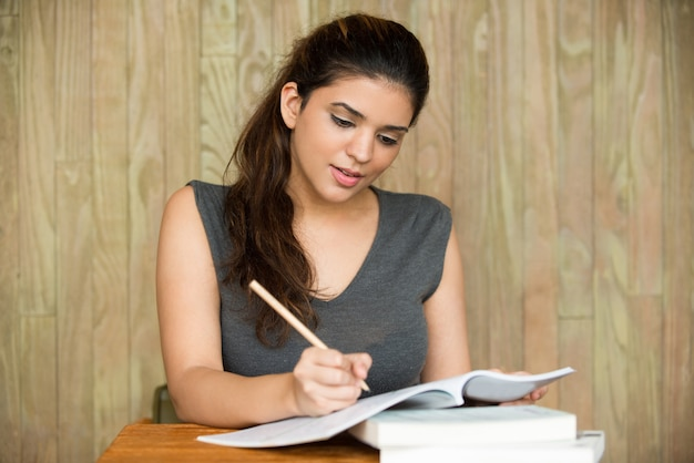 Portrait of smiling student writing in classroom