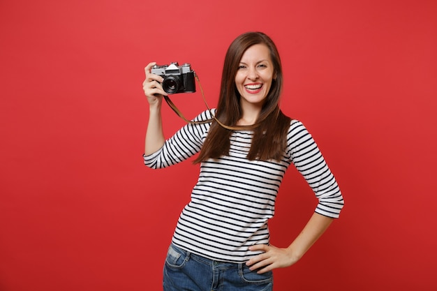 Portrait of smiling stunning young woman in striped clothes holding retro vintage photo camera isolated on bright red wall background. people sincere emotions, lifestyle concept. mock up copy space.