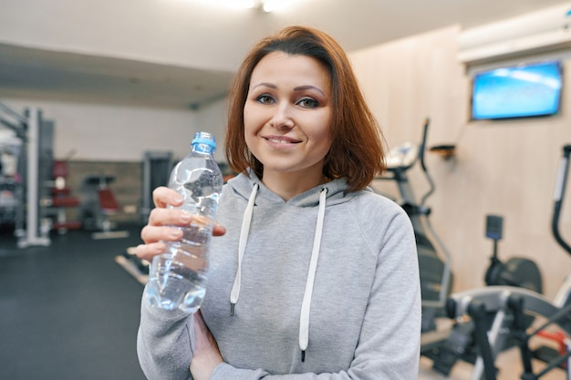 Portrait of smiling summer woman with bottle of water in gym.